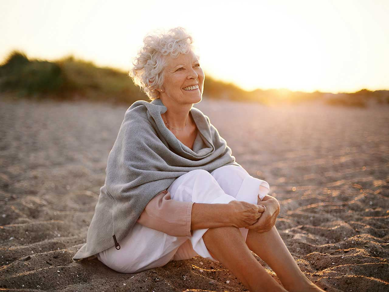 Mature woman sitting on the beach in sunlight enjoying retirement