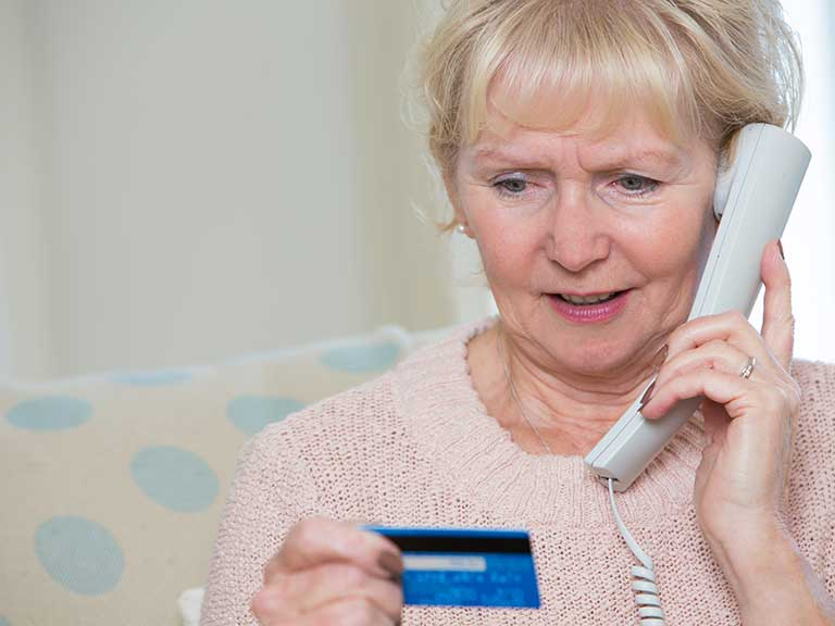 An older lady is confused about a cold calling phone call about pensions