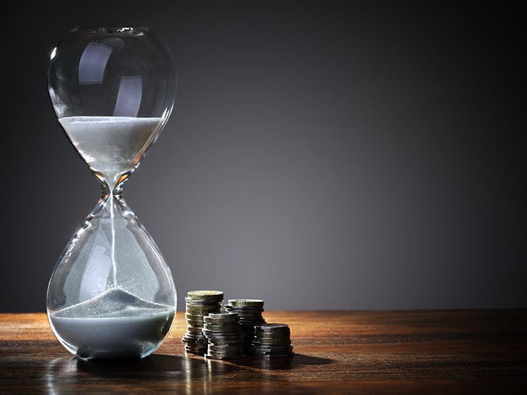An hourglass next to coins represent taking a pension early