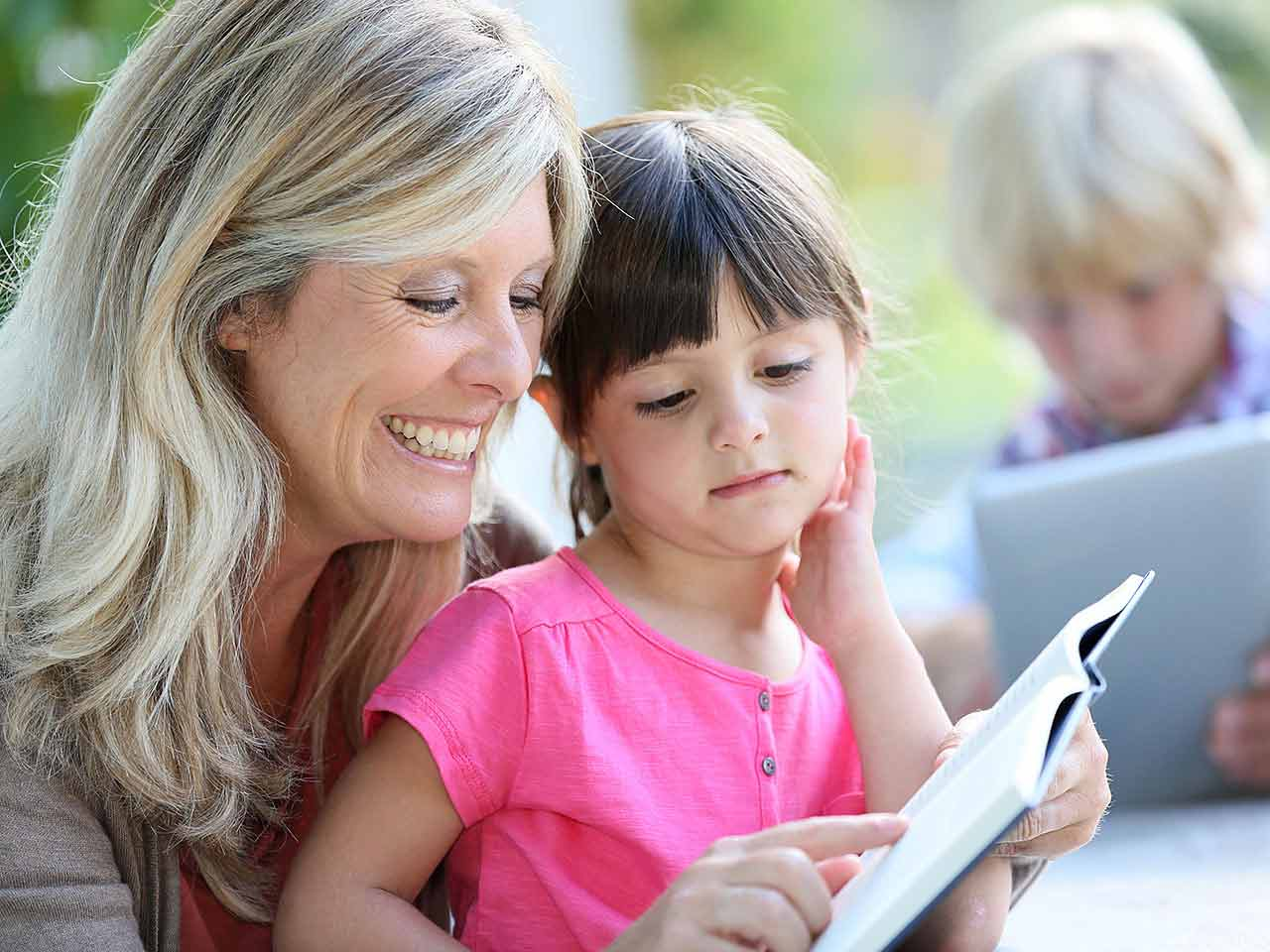 Mature lady teaching child to read