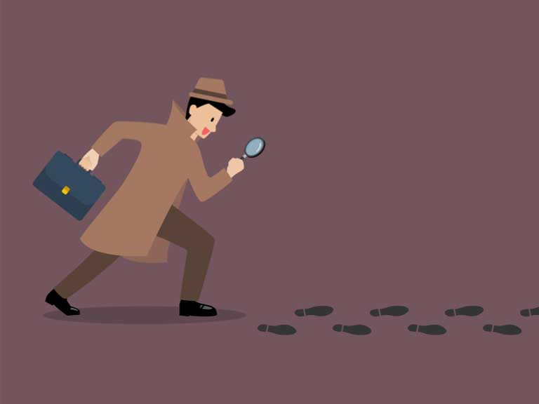 Image of a detective with a briefcase and magnifying glass following footprints