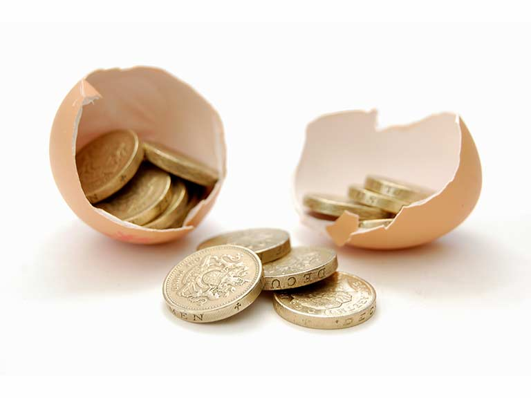 A cracked egg with pound coins to represent pension income