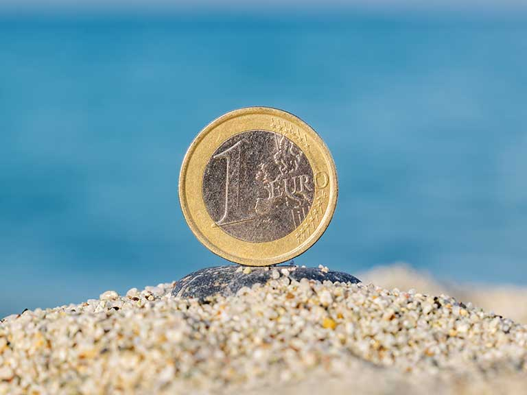 A euro coin on a sandy beach to represent moving a pension abroad