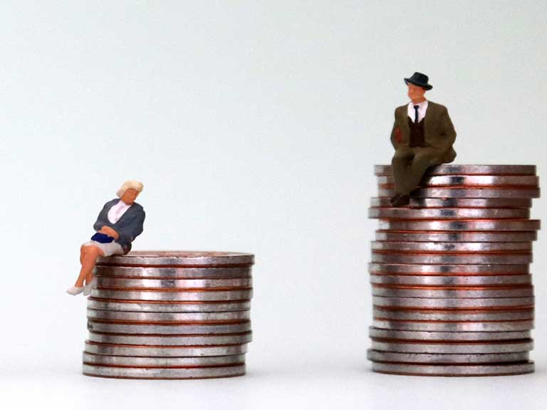 Miniature model of an oder woman sitting on small pile of coins next to a miniature model of an older man sitting on a taller pile of coins