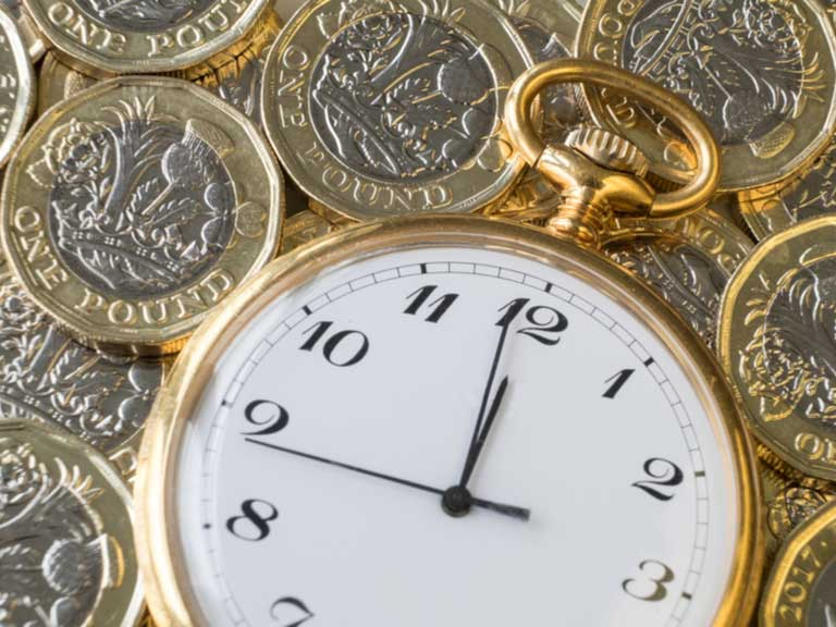 watch resting on a layer of pound coins