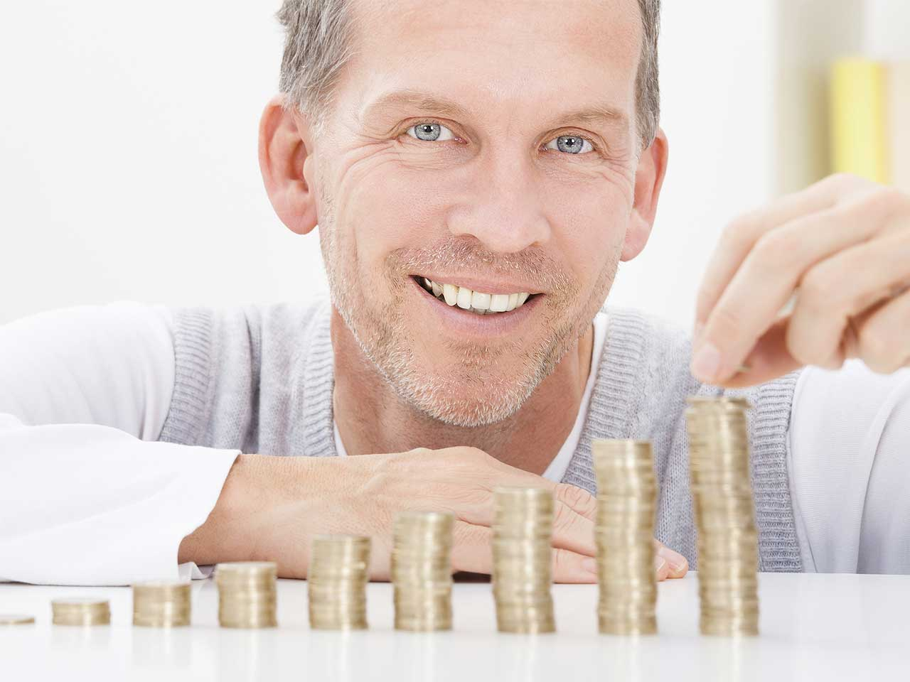 Mature man putting his money into piles to represent investing in an annuity.