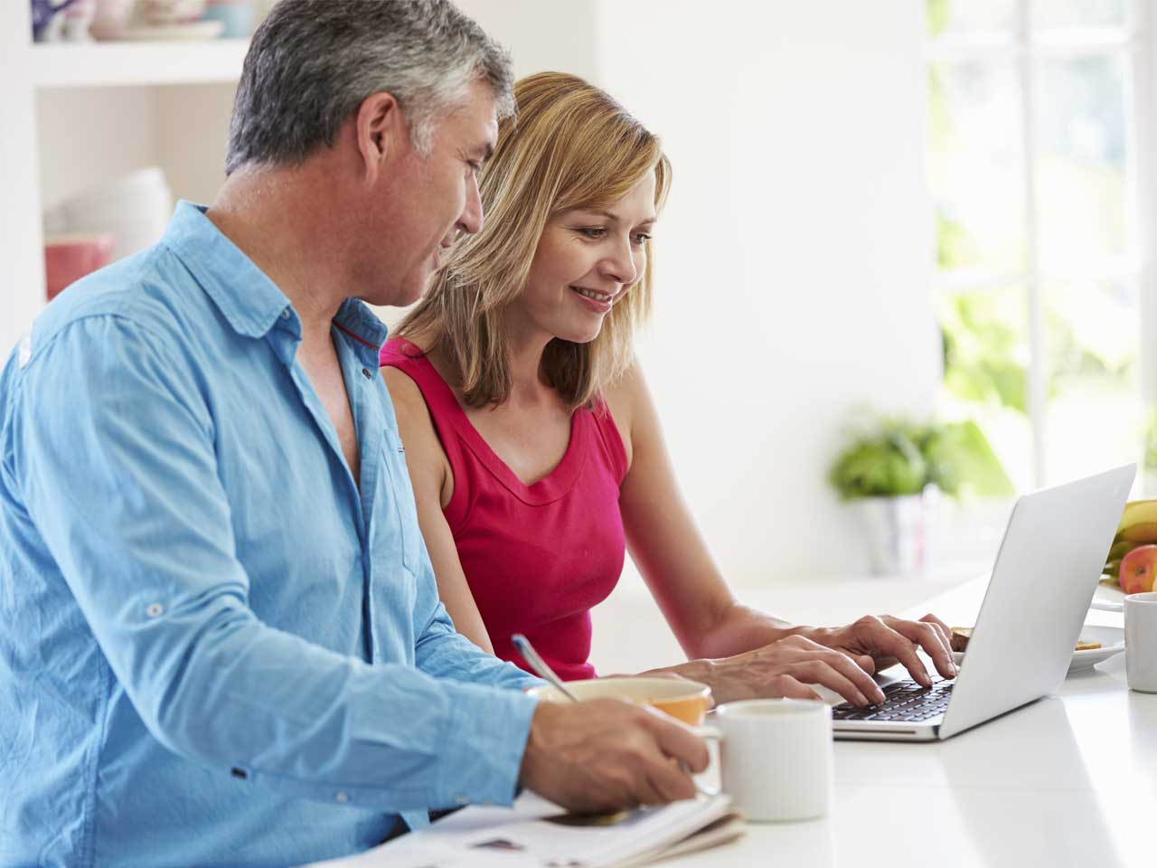 Couple reviewing their finances and pensions on a laptop