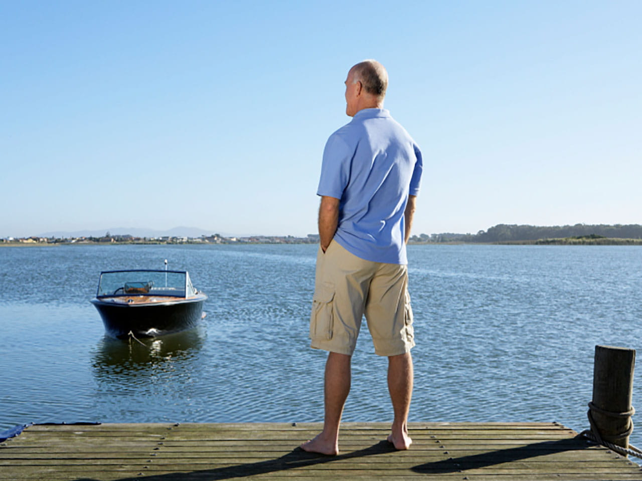 Man watching a boat at sea