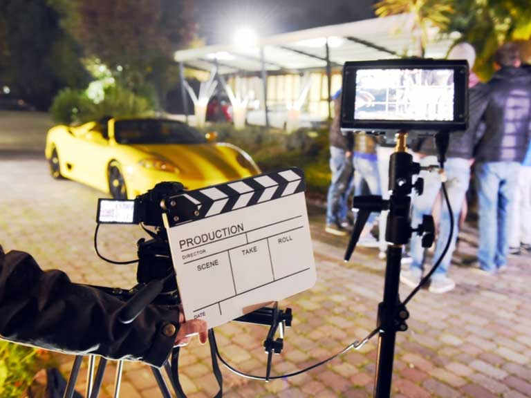 Film set at night with actors, film crew and lights set up
