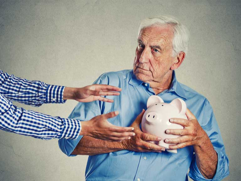 Older man holding piggy bank protectively away from grabbing hands