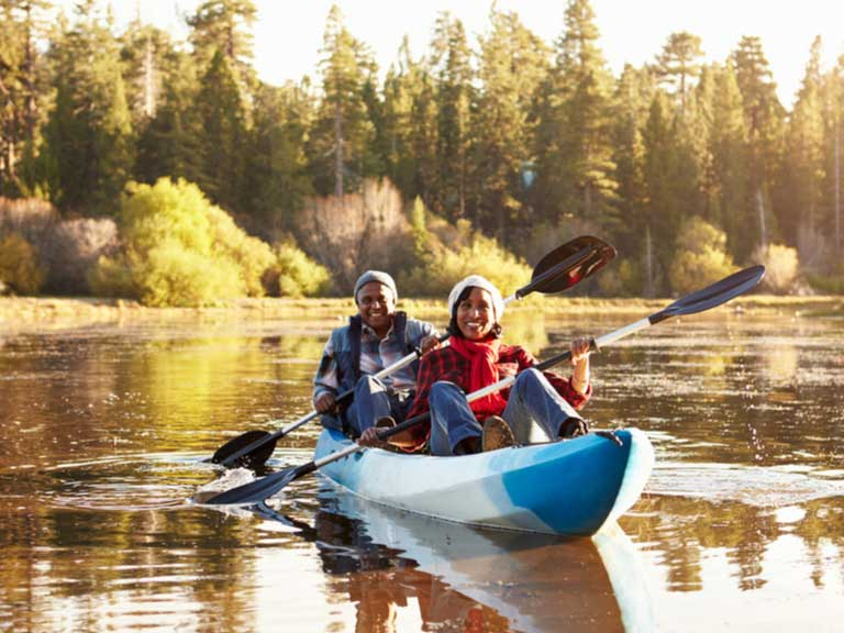 Senior couple in a kayak on a lake in a forest