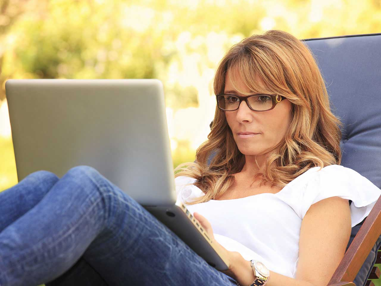 Mature lady researching on laptop in garden