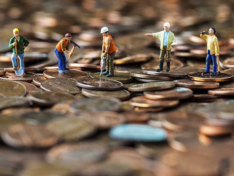 Model workmen standing on a pile of coins