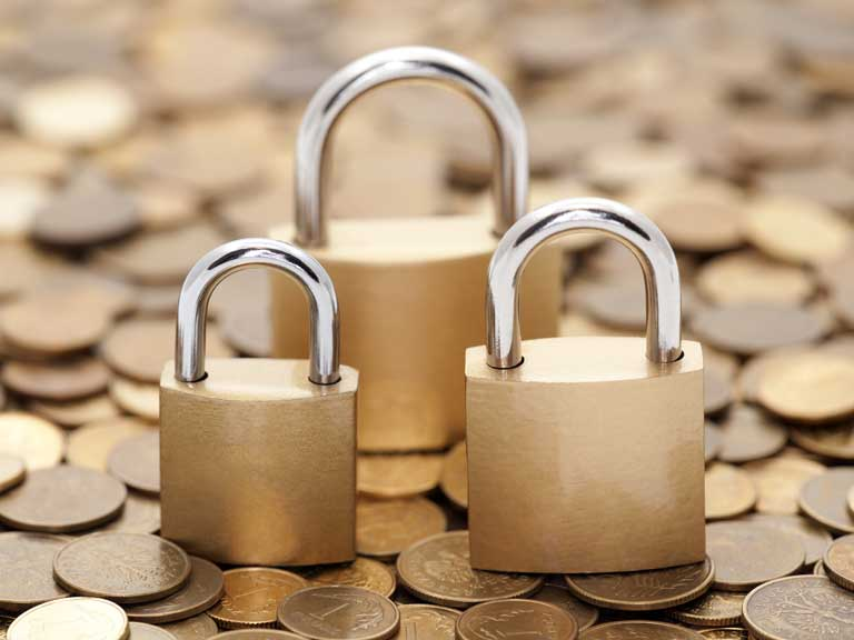 Money and a padlock to represent keeping your savings safe