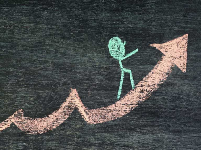 Chalk stick figure walking on an arrow pointing up