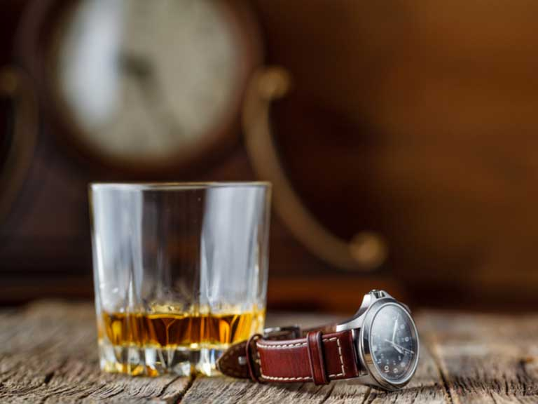 Glass of whisky with a watch beside it