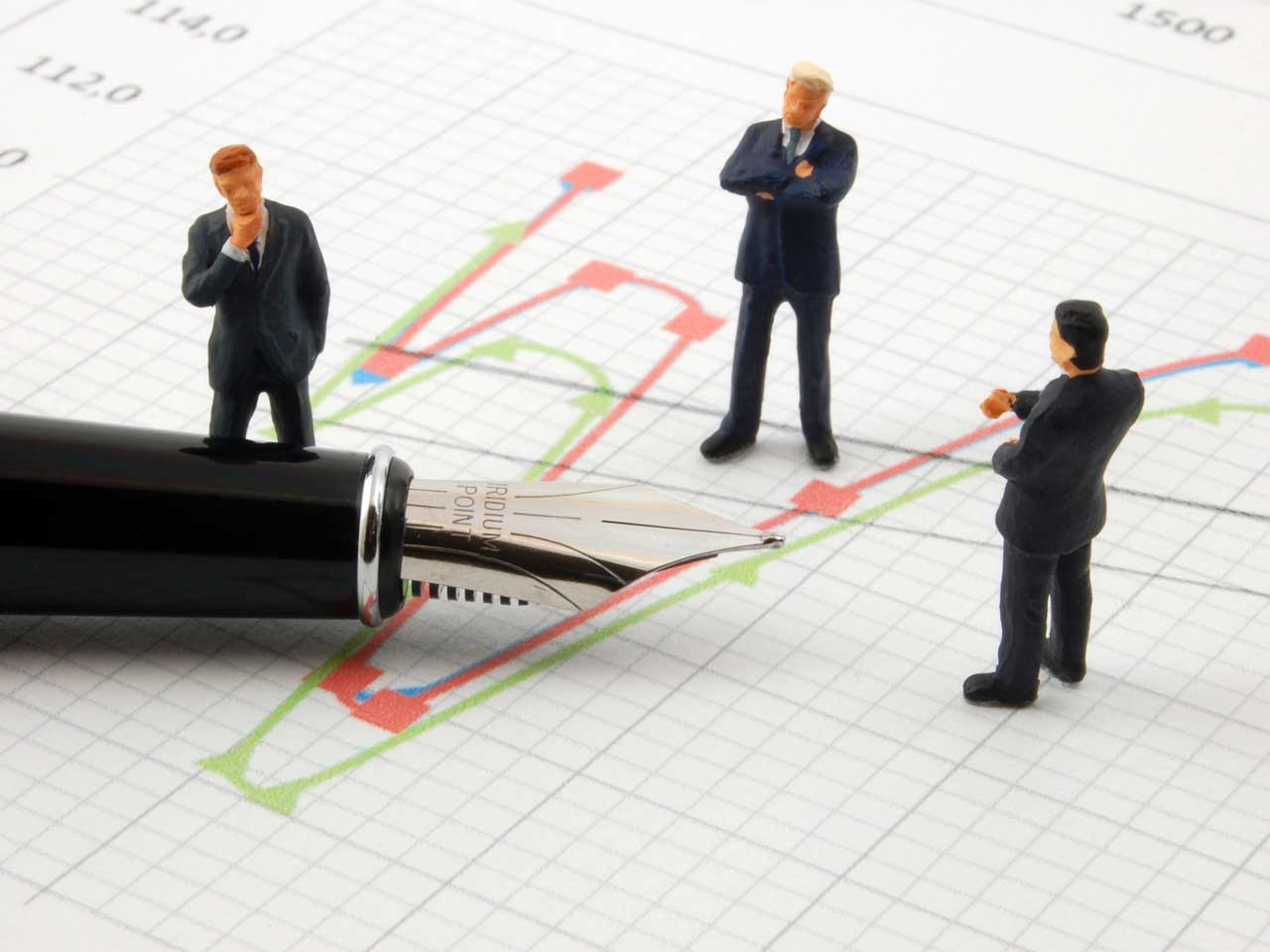 Figurines of stockbrokers looking at a stocks and shares graph