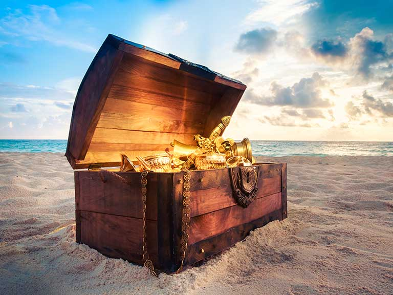 Pirate-style treasure chest on a beach, lid open and filled with gold, treasure and jewels