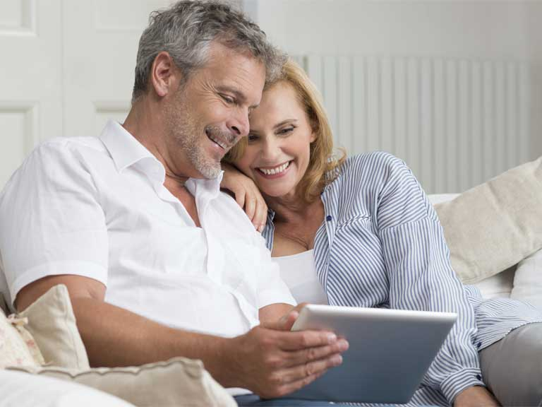Couple using a laptop to invest money for their retirement online