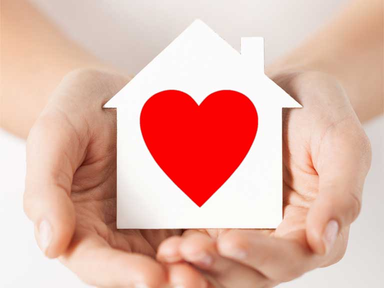 Image of a heart on a paper house to represent buying your first home.
