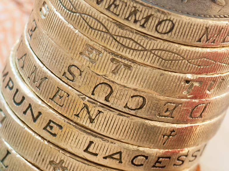 A pile of pound coins up close to represent watching your finances closely