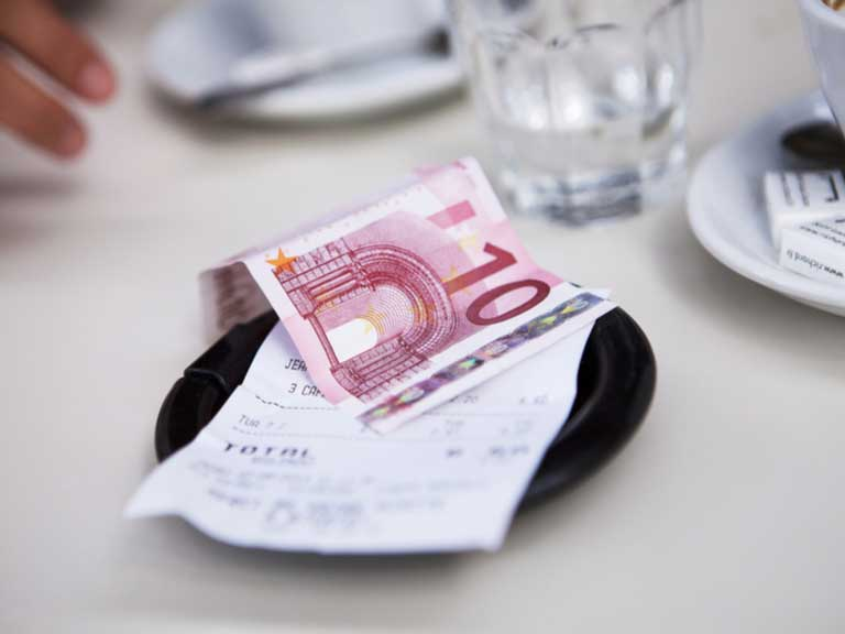 10 Euro note on top of a bill on a cafe table