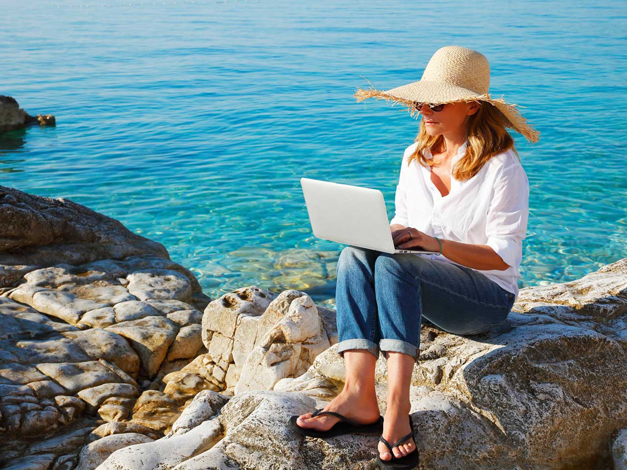 Woman using laptop while on holiday at the beach