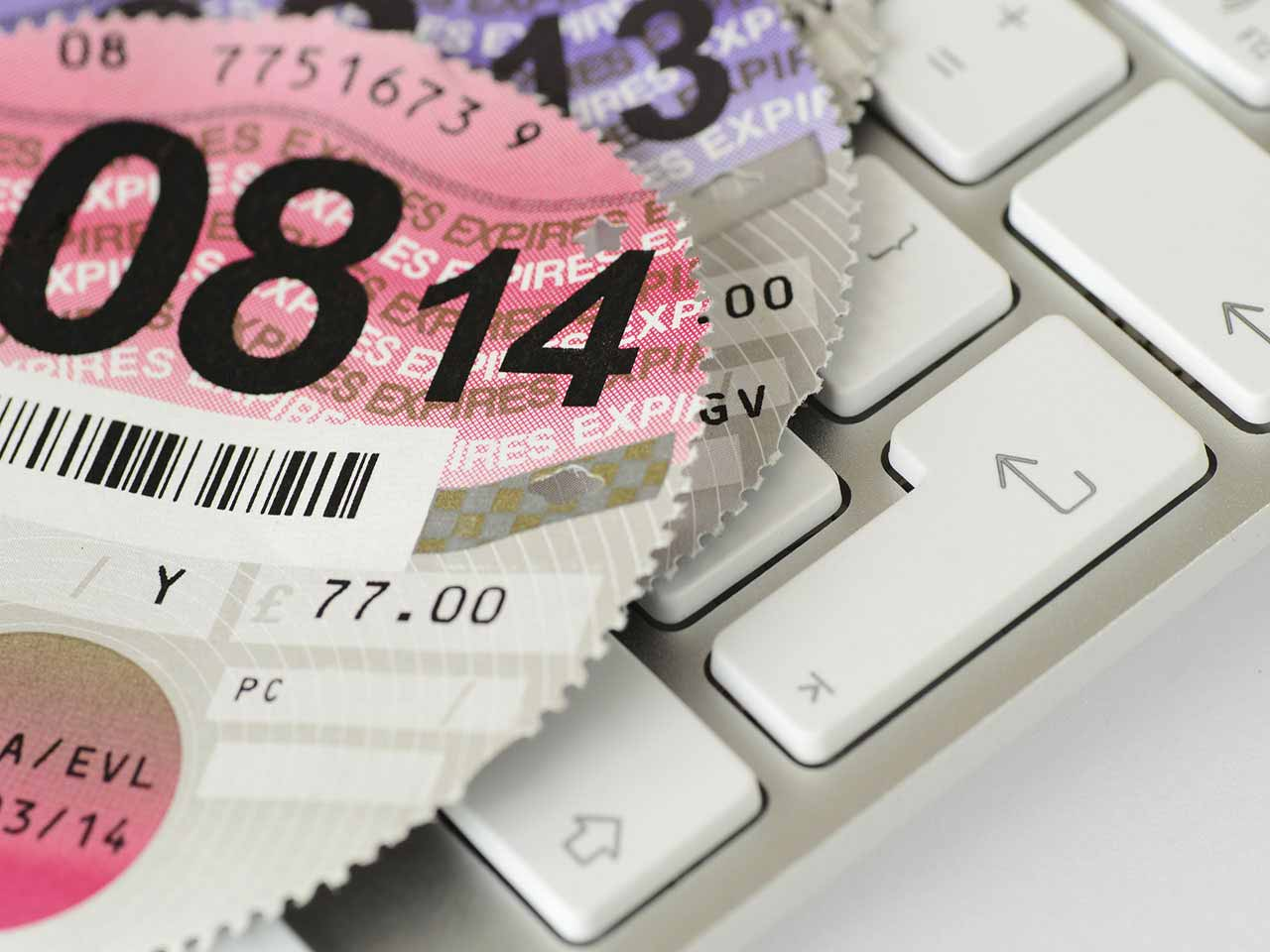 Road tax discs on a computer keyboard to represent the car tax refund email scam