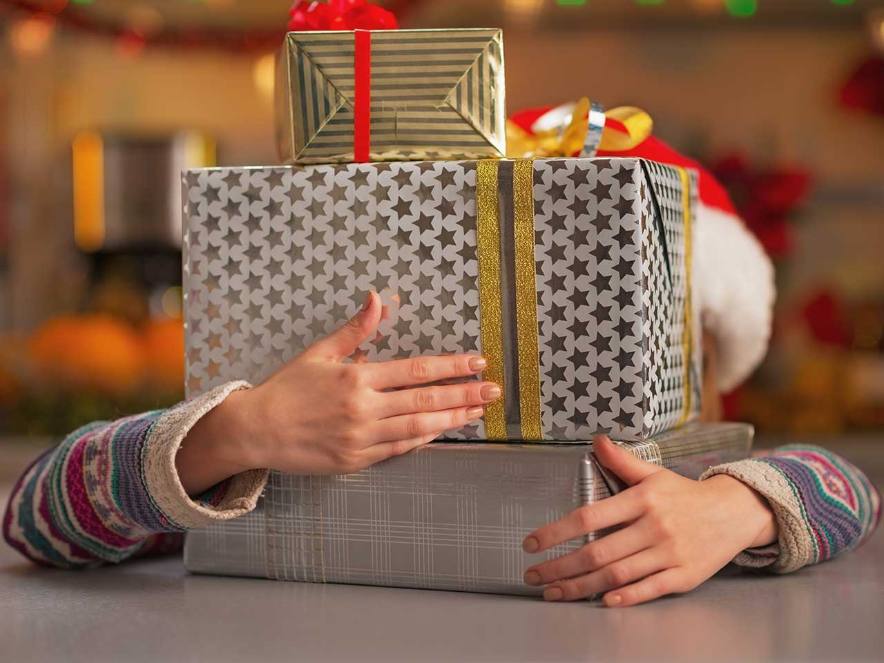 Girl hiding behind Christmas presents