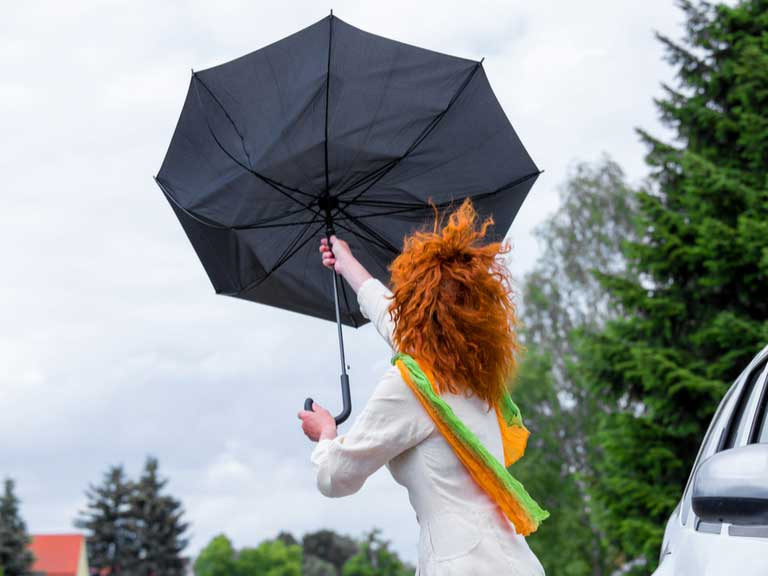 Woman holding an umbrella that has been turned inside out by a strong gust of wind