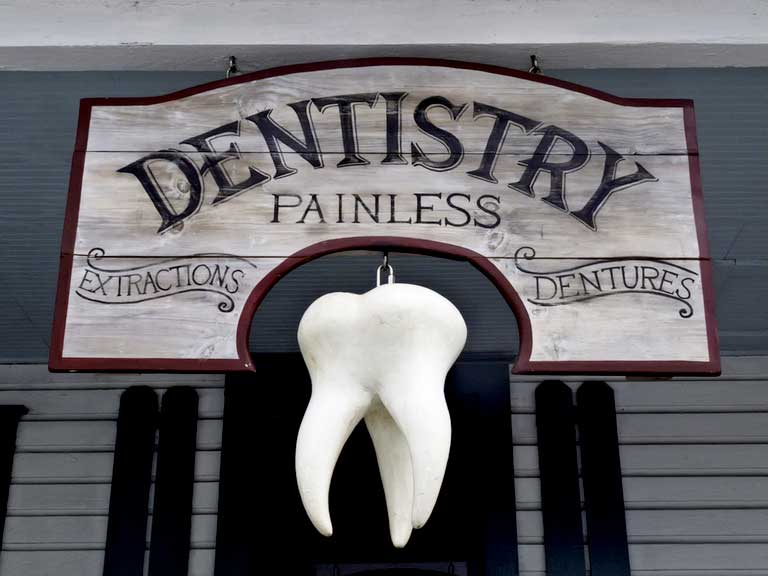 Old fashioned dentist sign with a large model tooth hanging beneath it.