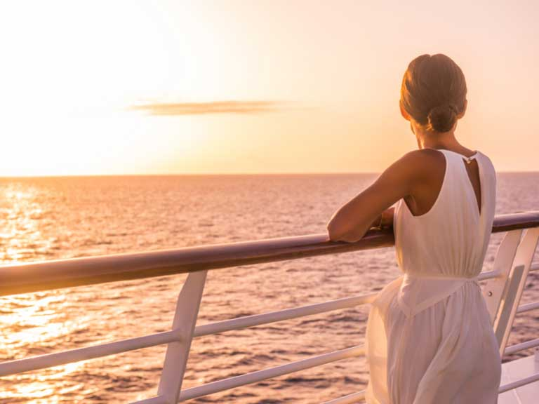 woman leaning on rail of cruise ship looking out to sea
