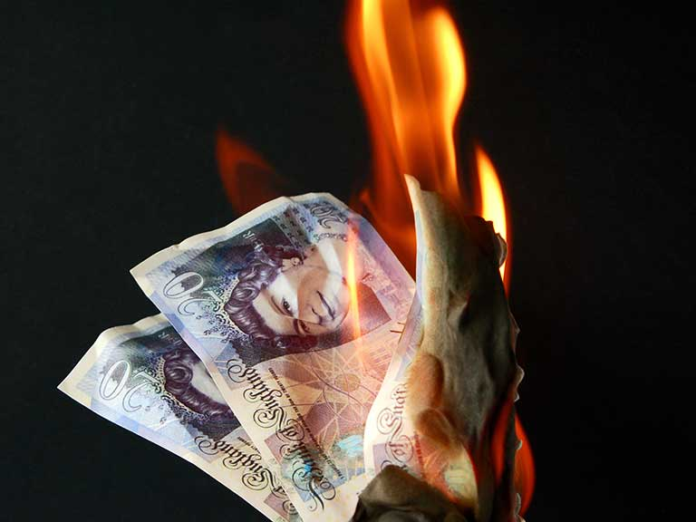 Burning money to represent investing in financial products you don't really need