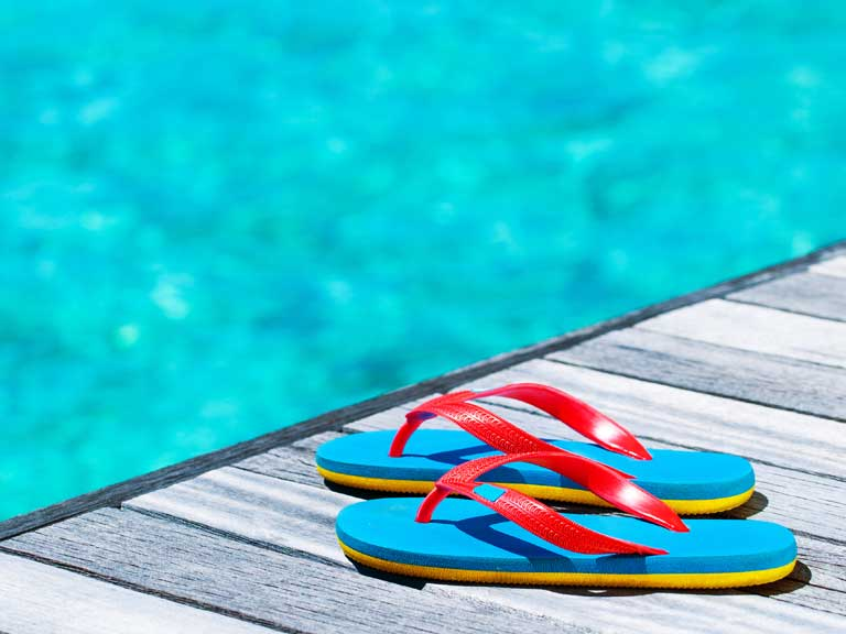 Sandals next to a swimming pool to represent a resort holiday