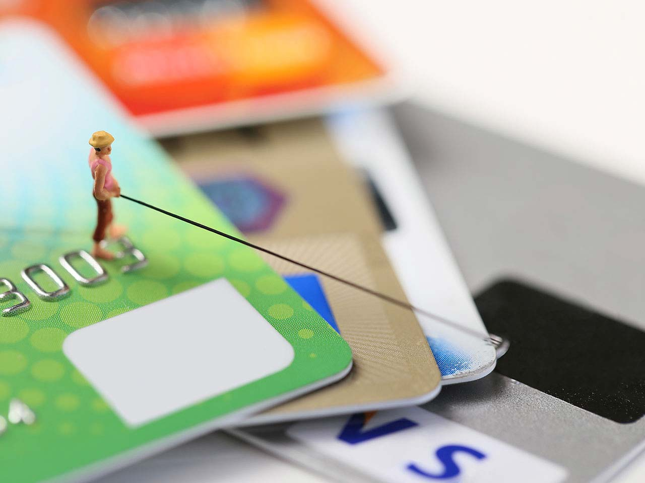 Model figure fishing and standing on credit cards