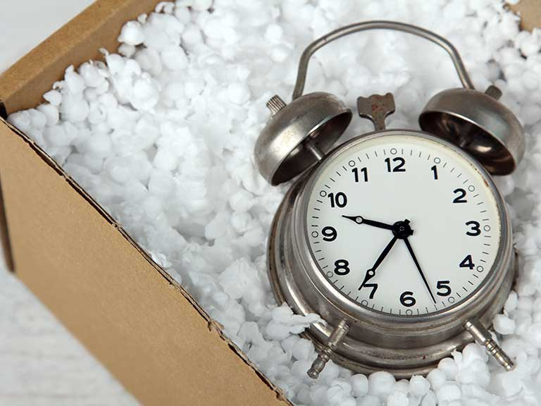 An alarm clock in a parcel to represent a late delivery