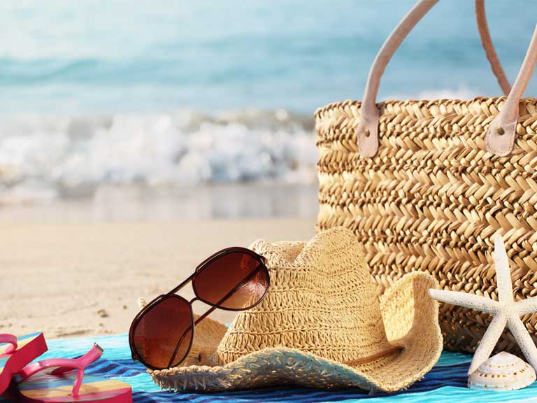 Holiday bag and sunglasses on a towel at the beach