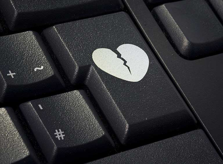A picture of a broken heart on a computer keyboard to represent a romance dating scam