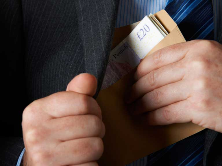Main in a suit putting envelope of sterling notes in jacket pocket