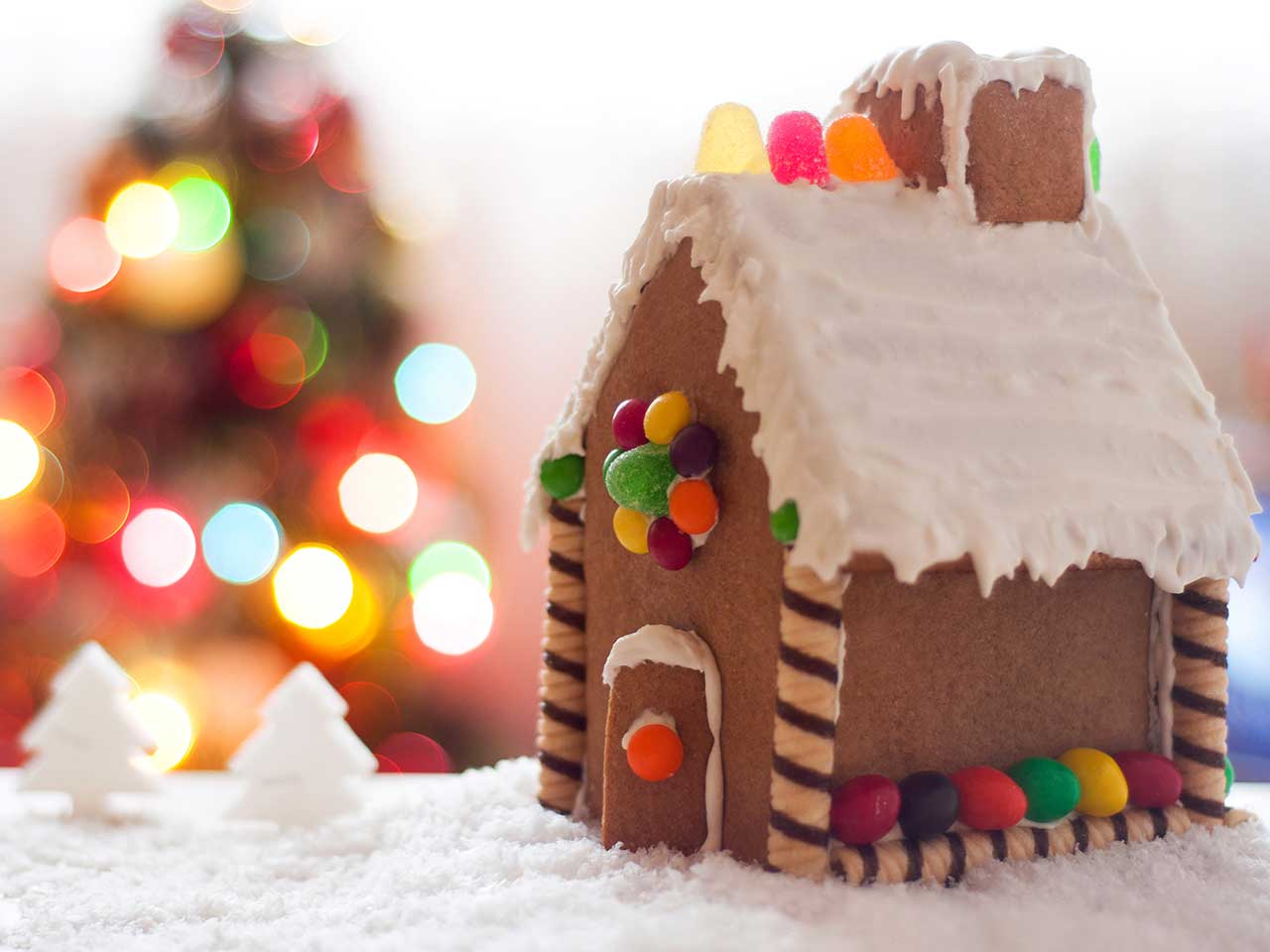 Gingerbread house with Christmas tree in the background