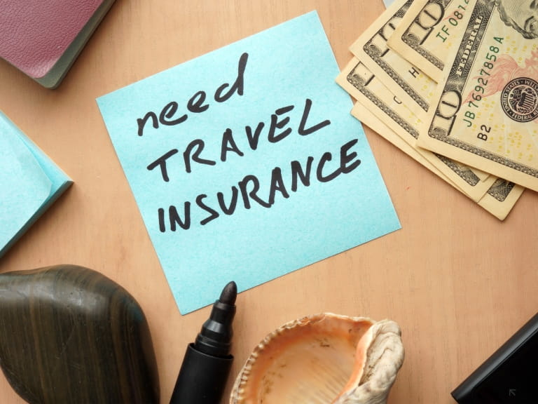 A post-it note reminder to buy travel insurance for a holiday
