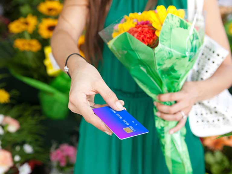 Woman holding bunch of flowers and paying by using her bank card