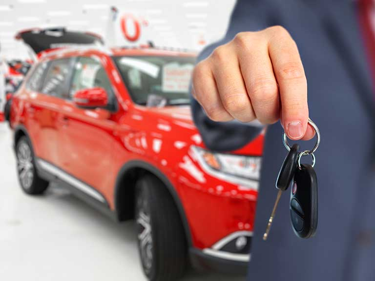 A salesman hands over the keys to a brand new car
