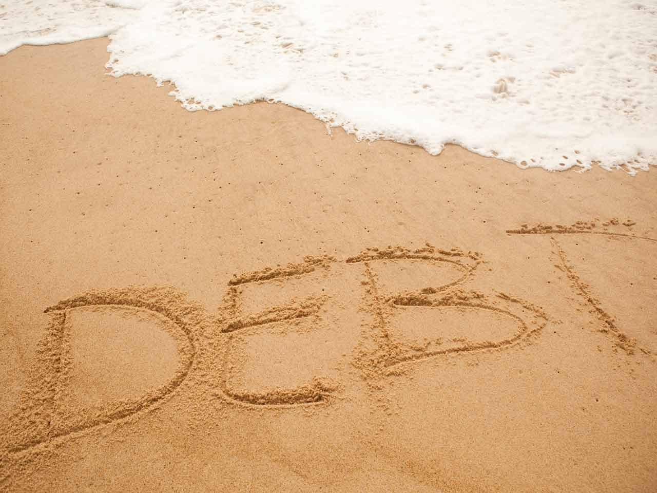 The word debt written in the sand being washed away