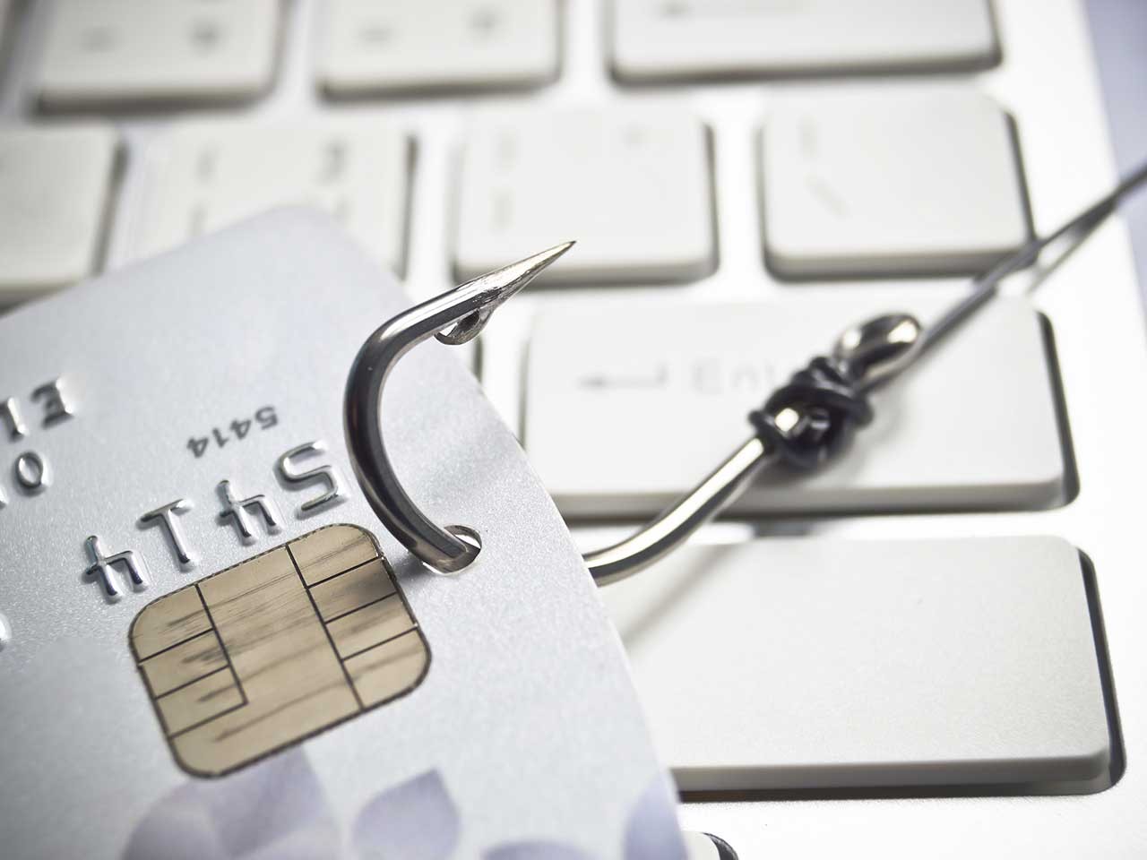 Fishing hook dragging a credit card across a computer keyboard to represent cyber crime
