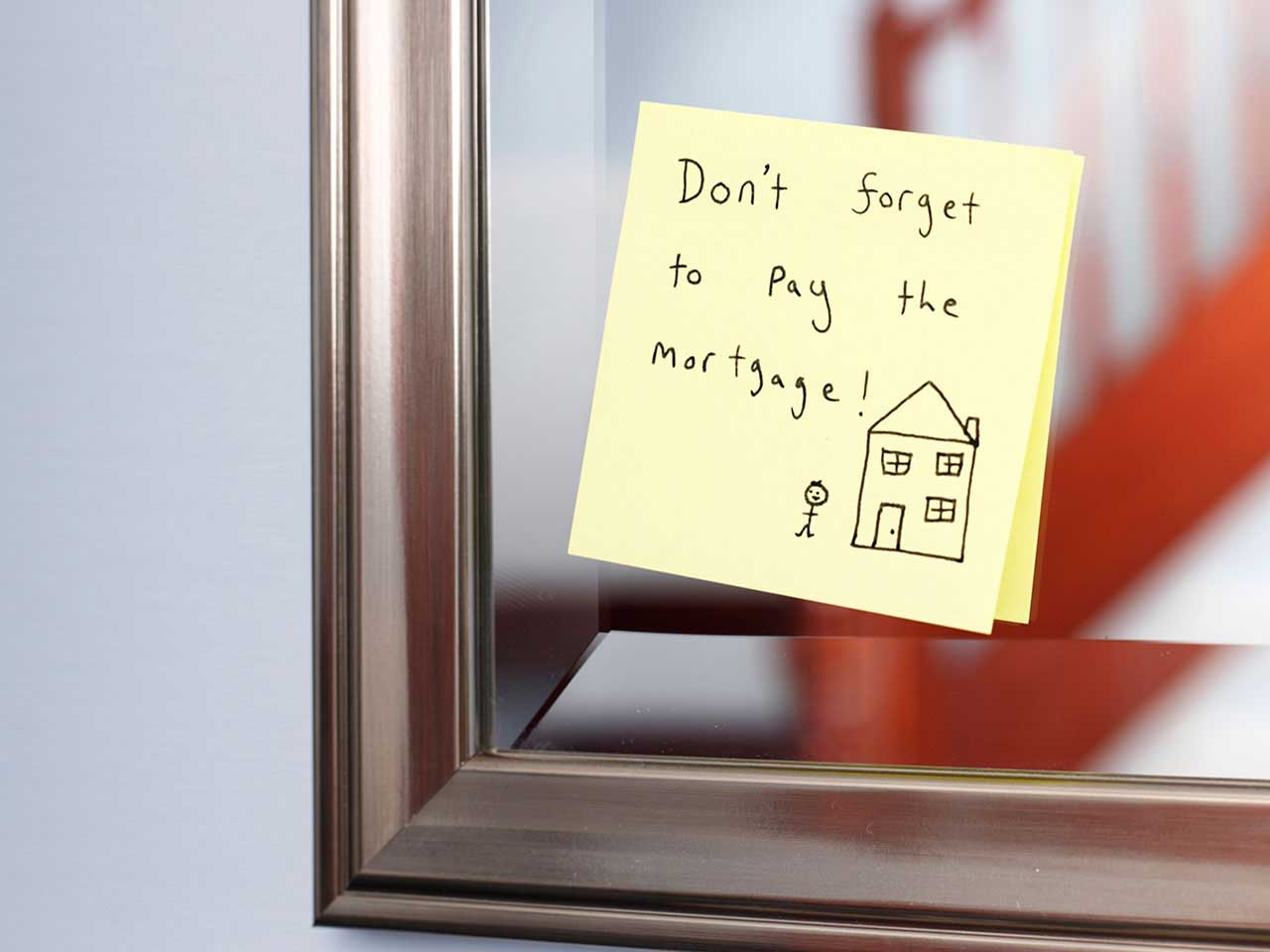 Reminder to pay mortgage on a post-it note stuck on a mirror