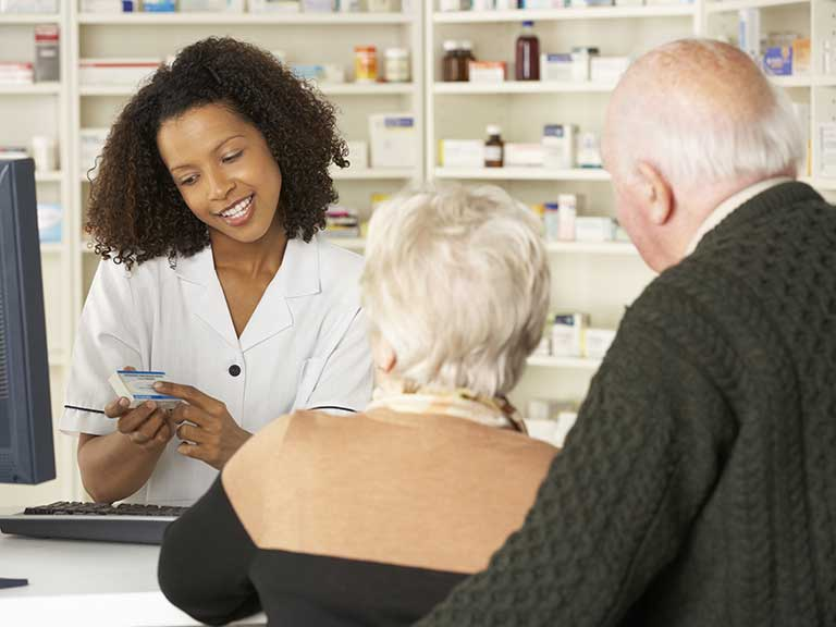 An older couple speak to the pharmacist about the minor ailment scheme