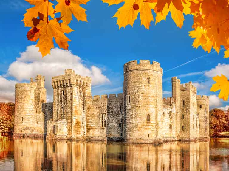 Bodiam Castle reflected in the moat on a sunny autumn day.