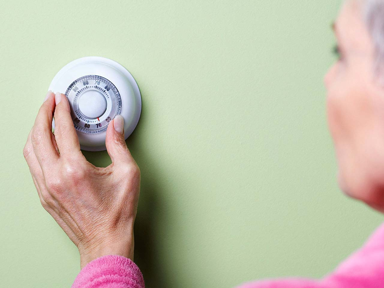 Mature lady turning down thermostat to save energy