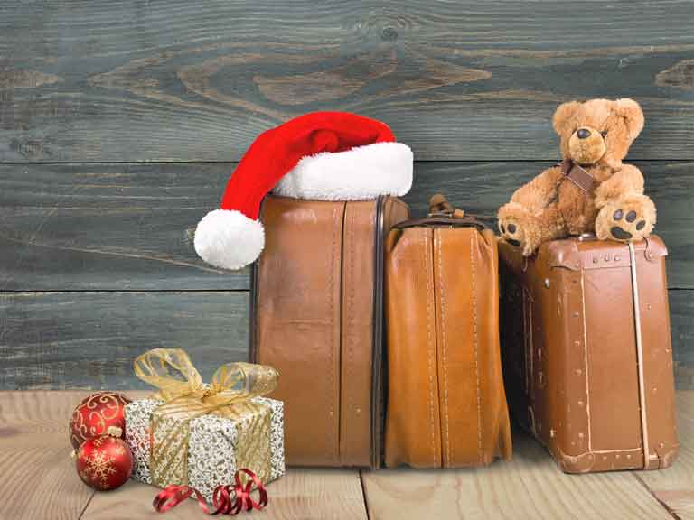 Three suitcases grouped together with a Santa hat and teddy on them, and presents on the floor